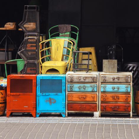 Colourful vintage furniture stacked up at the front of a vintage shop